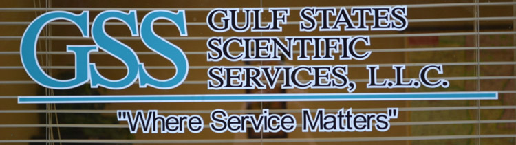 "A window inside of an office that reads: GSS - Gulf States Scientific Services, LLC - ""Where Service Matters"""